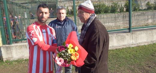 Foto a) Franzese consegna il mazzo di fiori a Pino Santonico